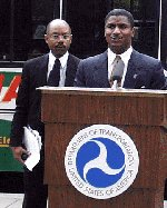Former U.S. Secretary of Transportation Rodney E. Slater giving some remarks during the electric bus ribbon-cutting ceremony at the U.S. Department of Transportation Headquarters Building in Washington, DC.  Former Federal Transit Administrator Gordon J. Linton is in the background.